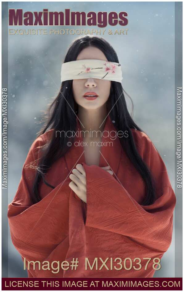 Beautiful asian woman with red sensual lips standing in the snow with a blindfold over her eyes