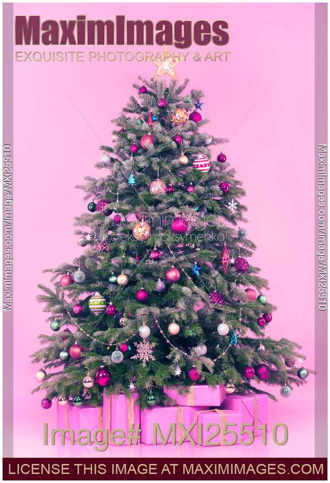 stock photo of decorated christmas tree with presents on pink background