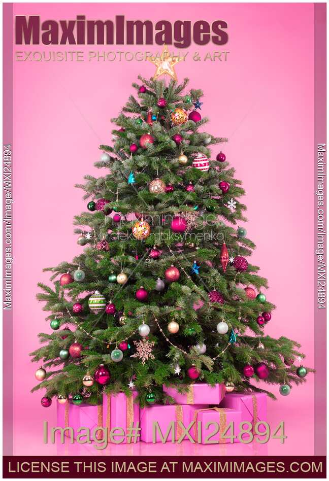 stock photo of decorated christmas tree with presents on pink