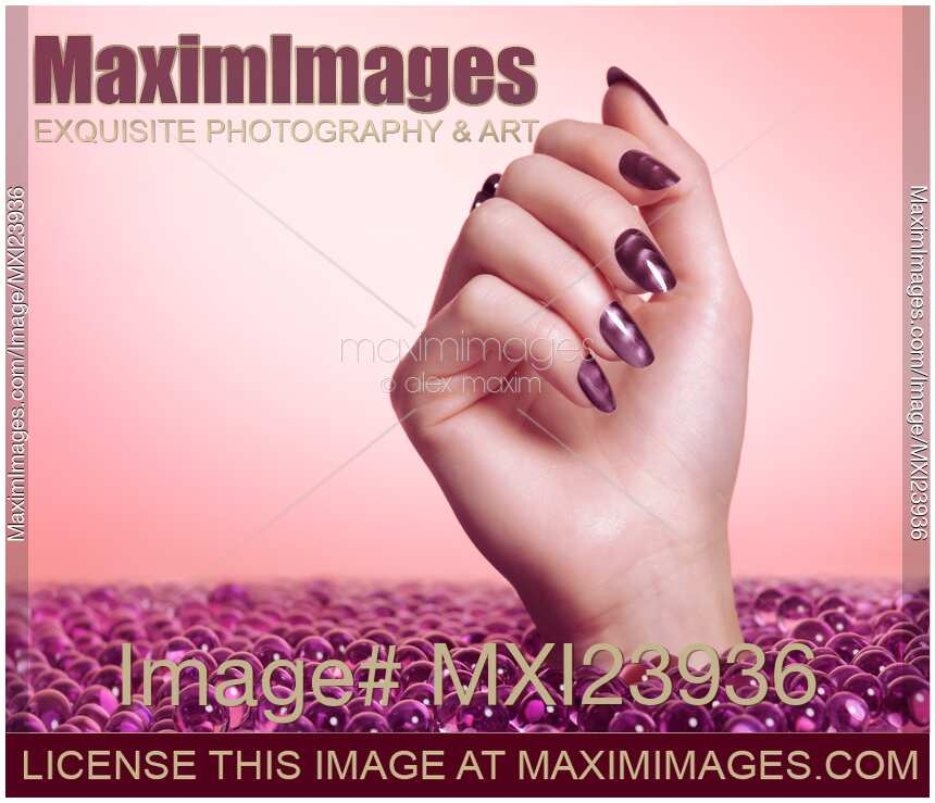 Stock photo of Woman Hand With Purple Nail Polish