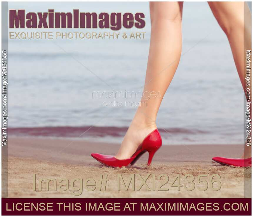 Stock photo of Woman walking in sexy high heel shoes on a sandy beach