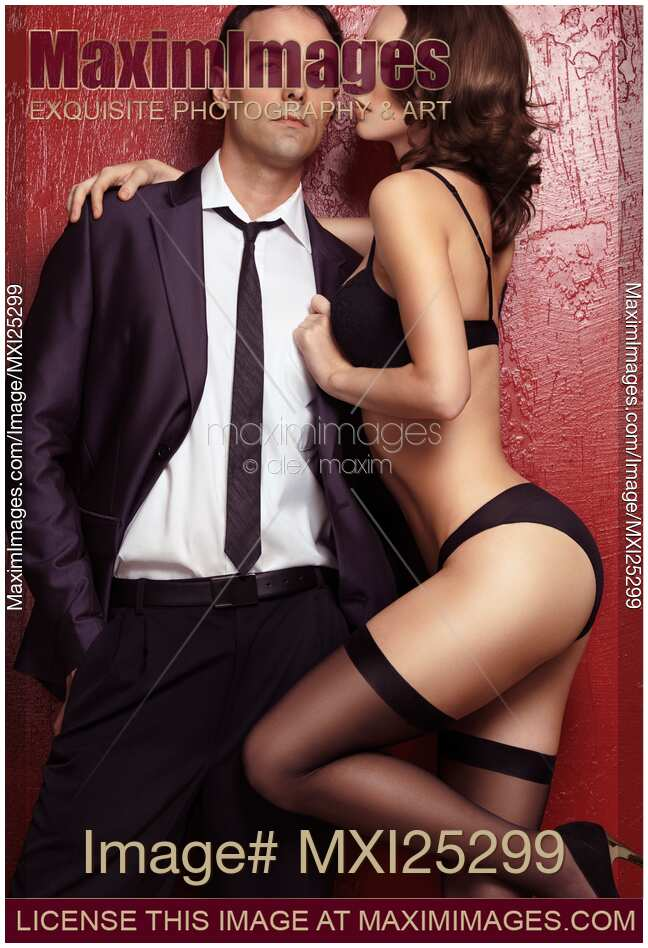 Stock photo of Young man in suit and sexy woman wearing lingerie