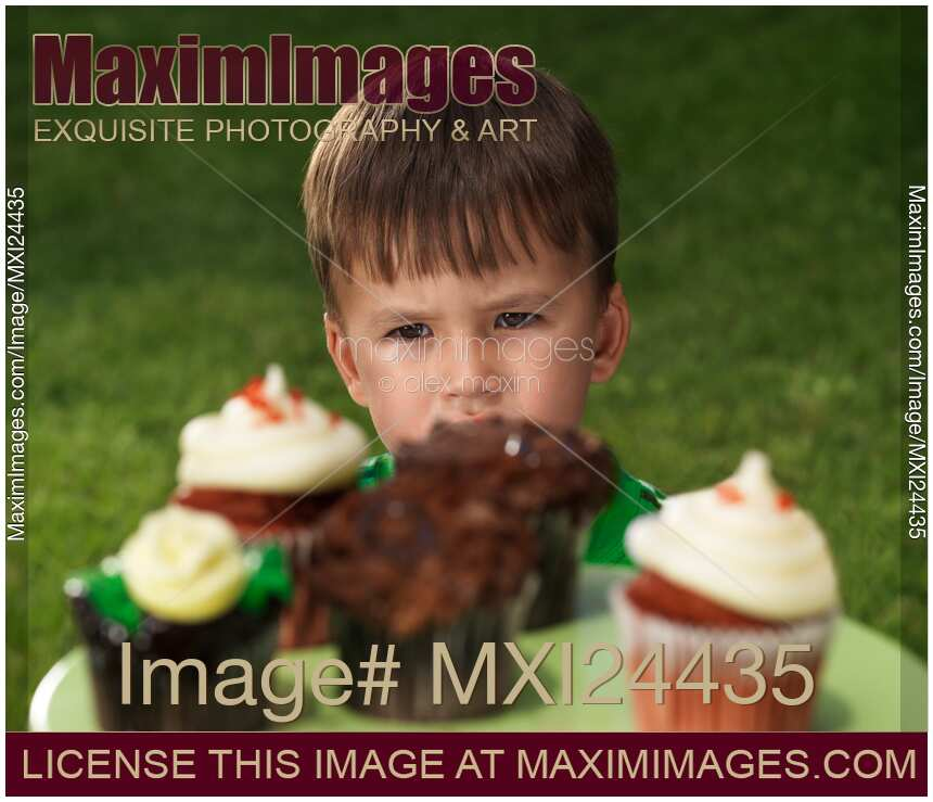 Stock photo of Little boy wants to eat all the cupcakes