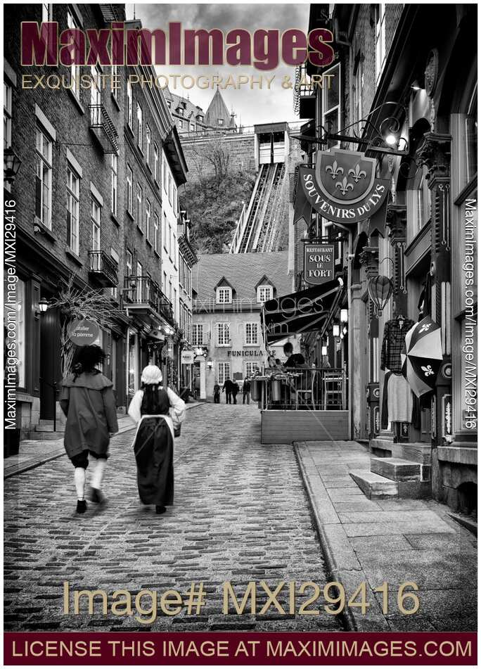 Two People In Medieval Costumes Walking Up The Rue Sous Le Fort Street Old Quebec City With Funicular Background Black And White Photo
