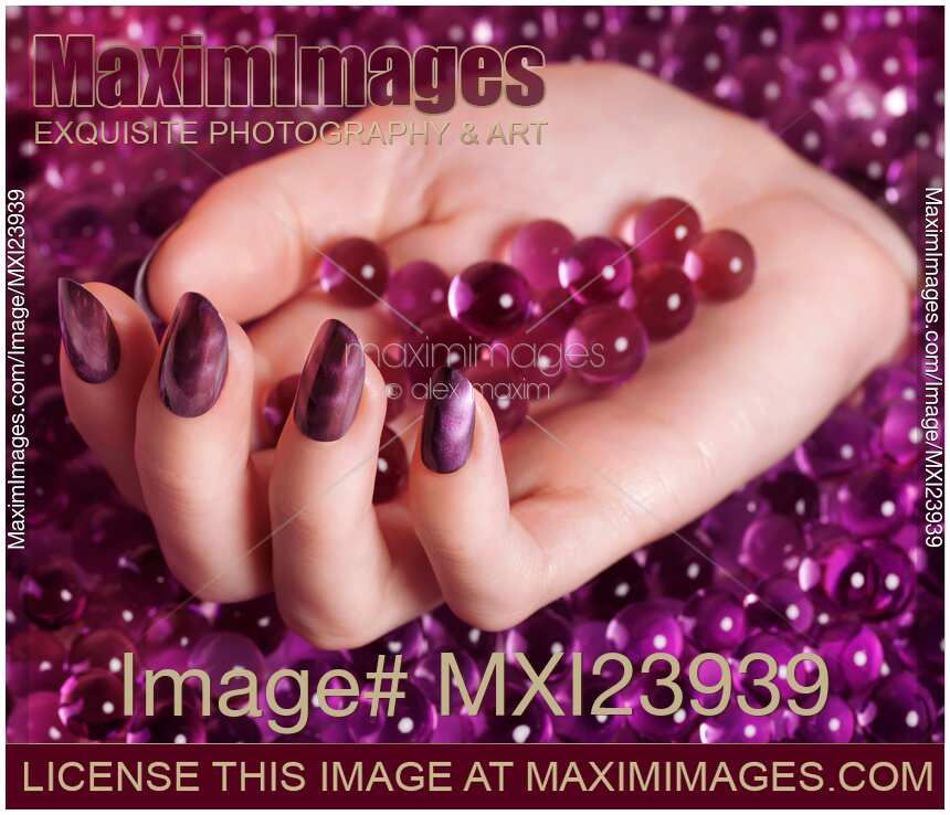 Nail Polish Colors For Younger Looking Hands: Stock Photo: Woman Hand With Purple Nail Polish On Candy