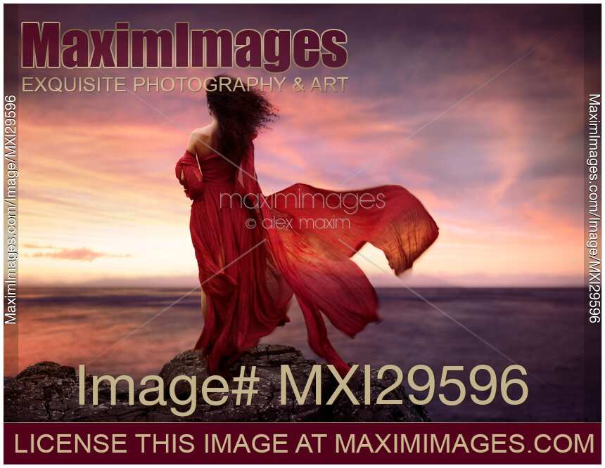 Woman in red dress flying in the wind looking at the ocean in sunset