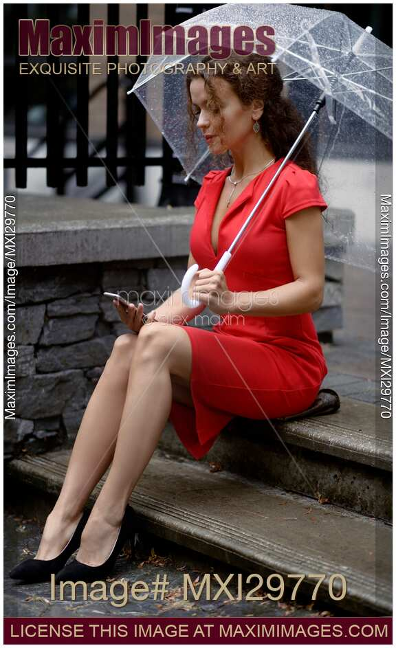 Woman in red dress sitting on the street under umbrella with cellphone