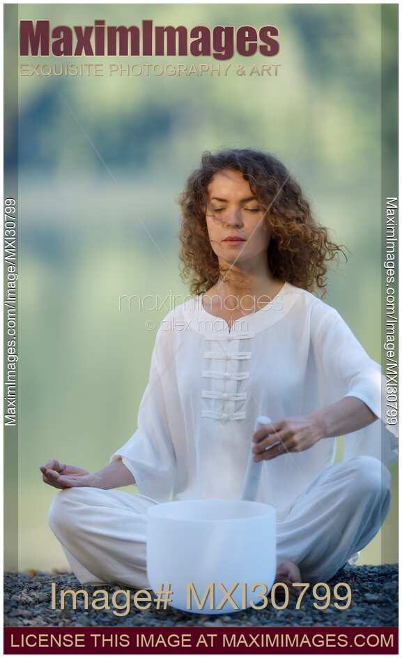 Woman meditating with a quartz crystal singing bowl in the morning by the lake in the nature