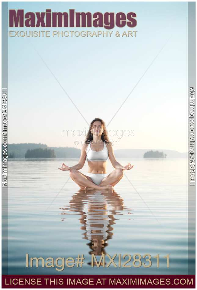 Woman practicing morning sunrise meditation on the water