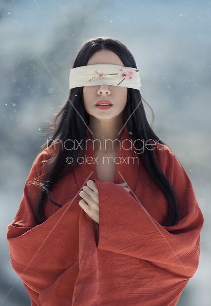 This Rights-Managed stock photo of Beautiful asian woman with red sensual lips standing in the snow with a blindfold over her eyes by Alex Maxim, is available for commercial, editorial or personal usage. You can buy a license of this image at MaximImages.com.