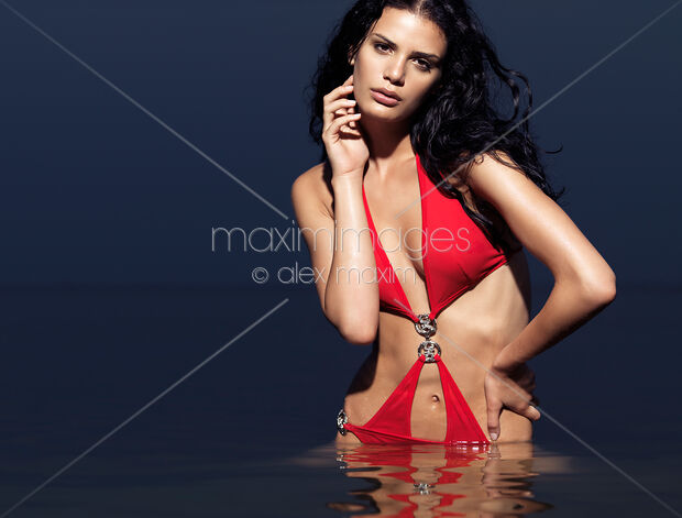 5b2ad9bd39a21 Beautiful young woman in red swim suit standing in water. High fashion  photo. | MaximImages stock photo