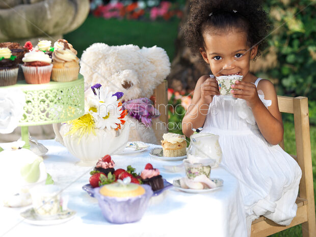 This Rights-Managed stock photo of Cute smiling girl drinking tea at a party table by Alex Maxim, is available for commercial, editorial or personal usage. You can buy a license of this image at MaximImages.com.