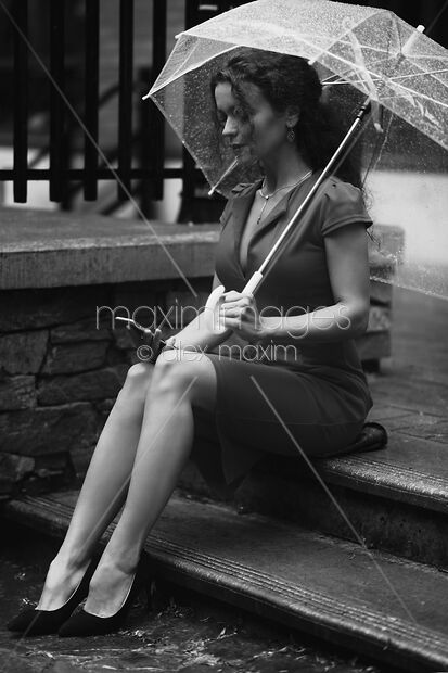 This Rights-Managed stock photo of Elegant woman in a dress sitting on the street under umbrella with a phone Black and white by Alex Maxim, is available for commercial, editorial or personal usage. You can buy a license of this image at MaximImages.com.
