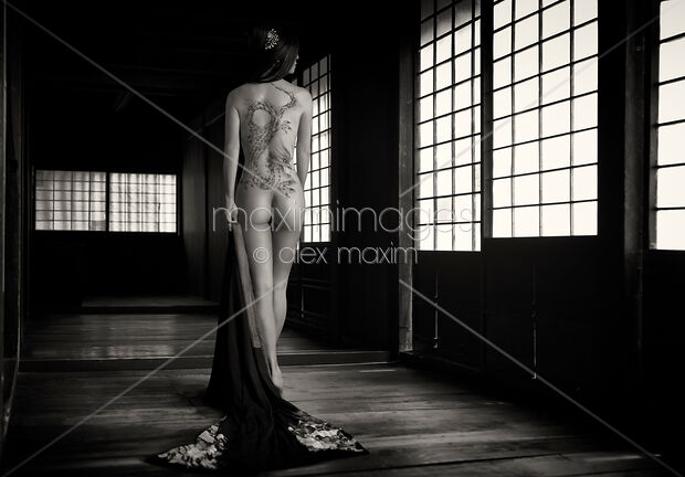 This Rights-Managed stock photo of Mysterious Japanese woman with a dragon tattoo of Yakuza clan on her naked back in a dark empty house Black and white nude art by Alex Maxim, is available for commercial, editorial or personal usage. You can buy a license of this image at MaximImages.com.