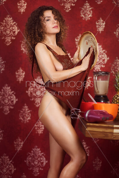 Stock Photo Of Sexy Young Pretty Woman Cooking A Meal Wiping A Plate Thoughtfully With Her Image MXI31368 At