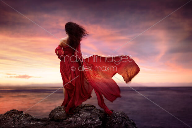 This Rights-Managed stock photo of Woman in red dress flying in the wind looking at the ocean in sunset by Alex Maxim, is available for commercial, editorial or personal usage. You can buy a license of this image at MaximImages.com.