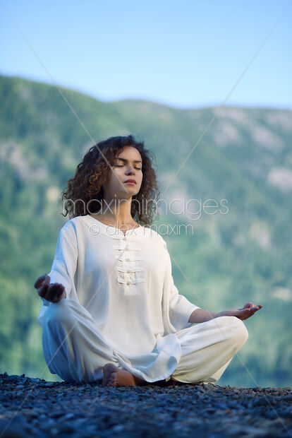 Stock photo of Woman meditating in the morning sunrise in the nature