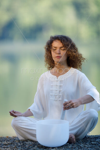 This Rights-Managed stock photo of Woman meditating with a quartz crystal singing bowl in the morning by the lake in the nature by Alex Maxim, is available for commercial, editorial or personal usage. You can buy a license of this image at MaximImages.com.