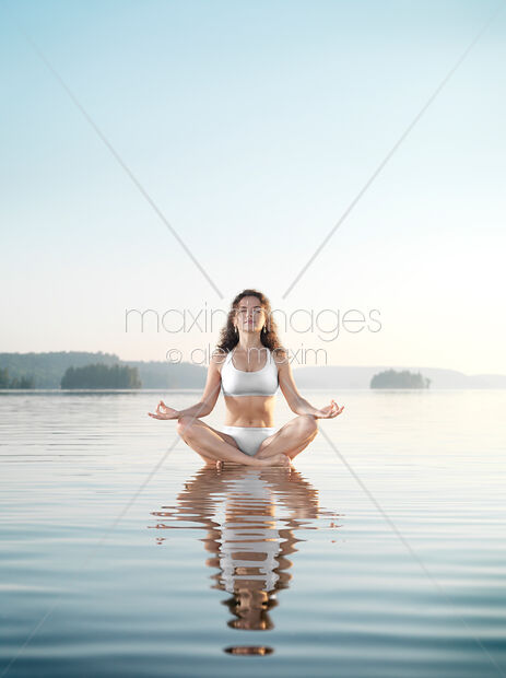 This Rights-Managed stock photo of Woman practicing morning sunrise meditation on the water by Alex Maxim (Oleksiy Maksymenko), is available for commercial, editorial or personal usage. You can buy a license of this image at MaximImages.com.