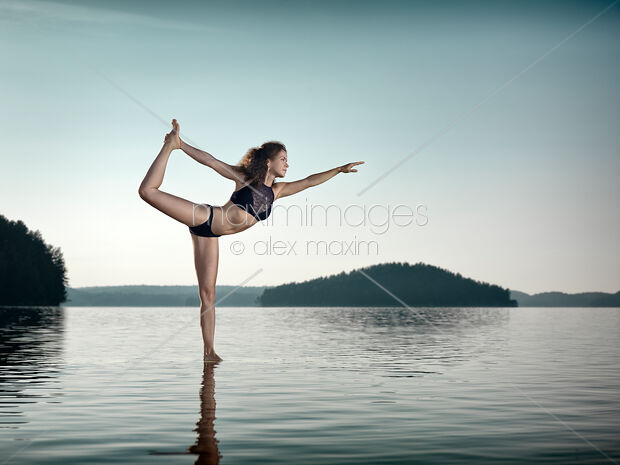 Woman practicing yoga on platform in the water doing Dancer pose