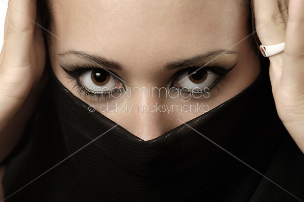 4e1aa73eb0b Beauty portrait of an exotic young woman with beautiful eyes covering her  face with a black scarf.