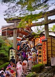 People entering Torii gate to Jishu-Jinja shrine at Kiyomizu-dera Buddhist temple in Kyoto Japan