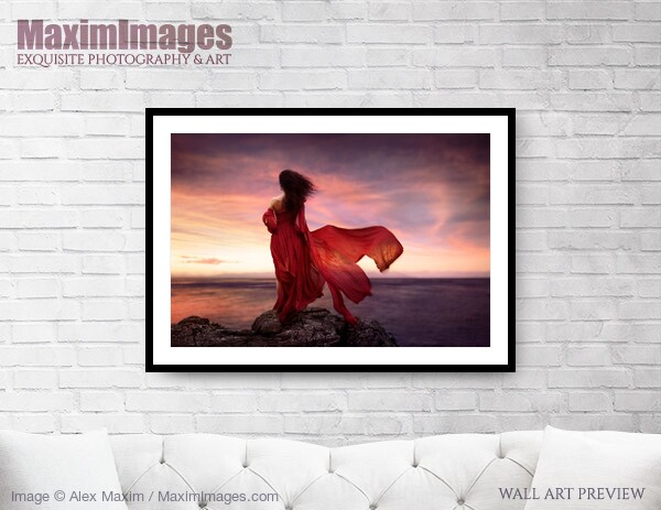 This Fine Art Print of Woman in red dress flying in the wind looking at the ocean in sunset by Alex Maxim, is available in different sizes and paper finishes. You can buy this Wall Art at MaximImages.com.